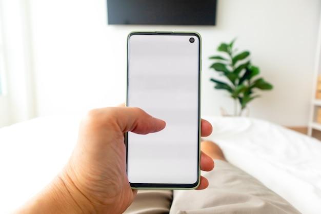 ベッドの上でスマートフォンを使用している男性の一人称ビュー。