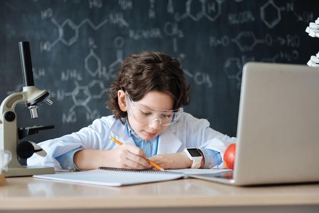 내 인생의 첫 번째 scince 워크샵. 실험실에 앉아 메모를하고 기기를 사용하면서 미생물학 수업을 즐기는 매력적인 부지런한 똑똑한 아이