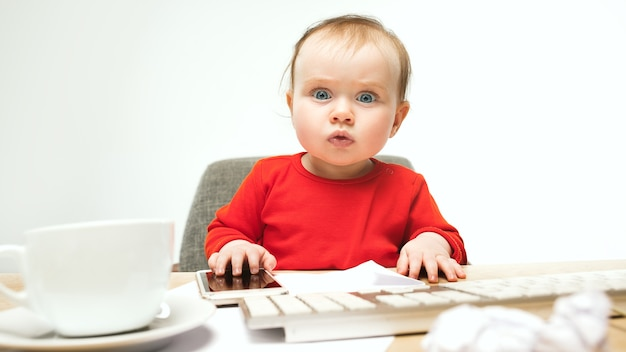 First sms. child baby girl sitting with keyboard of modern computer or laptop in white studio