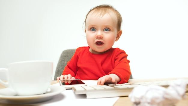 Первое смс. ребенок девочка сидит с клавиатурой современного компьютера или ноутбука в белом
