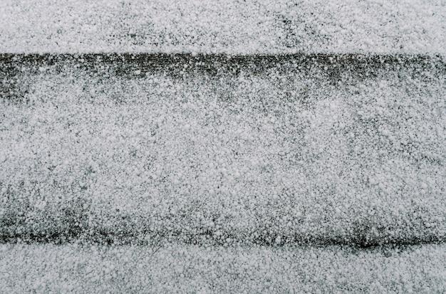 古びた板が並んだ淡い色あせた茶色と涼しい青の再生された松の木の表面の最初の雪