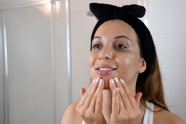 Первый шаг - удаление макияжа очищающим маслом. красивая молодая женщина с помощью экологически чистого очищающего масла для удаления макияжа без ватного диска.