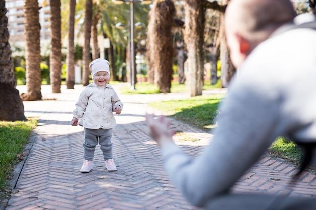 最初のステップの概念-夏の公園で父親と一緒に歩くことを学ぶ小さな女の赤ちゃん