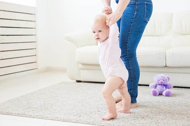 最初のステップ。歩くことを学ぶ小さな女の赤ちゃん。白い背景でスタジオ撮影