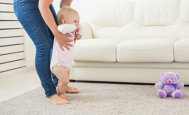 最初のステップ。歩くことを学ぶ小さな女の赤ちゃん。
