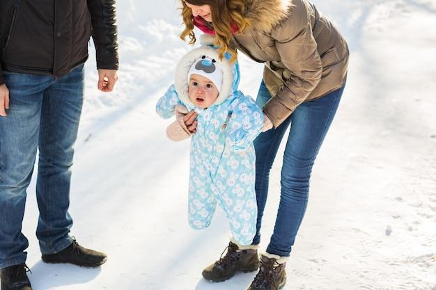 첫 번째 단계입니다. 걷는 법을 배우는 작은 아기. 겨울 공원에서 유아 소년과 어머니와 아버지