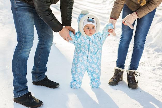 Первые шаги ребенка в зимнем парке.