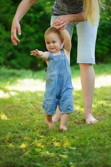 草の上の母親からの赤ちゃんの最初のステップ