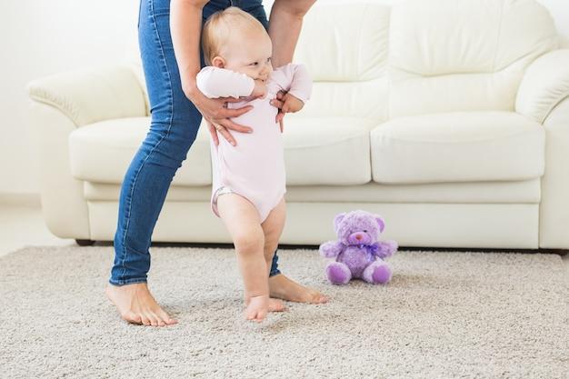 白い日当たりの良いリビングルームで歩くことを学ぶ幼児の最初のステップ。子供用の靴。