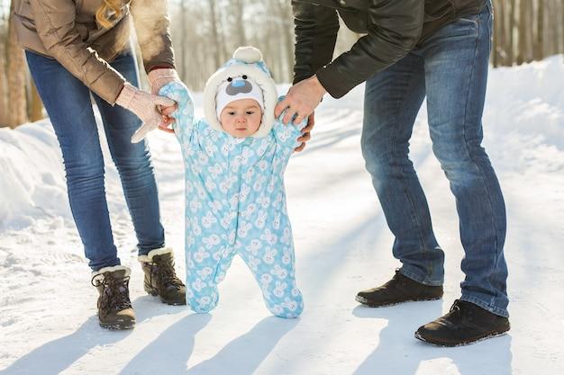Первые шаги маленького мальчика в зимнем парке.