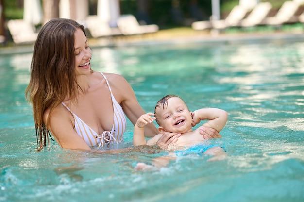 最初にプールで泳ぎました。彼女の幼い息子と一緒にプールで泳いでいる長い髪の若い女性
