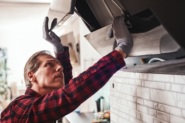 First technical aid closeup of young man repairs exhaust hood