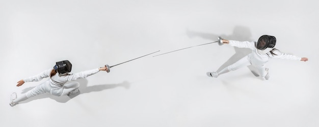 First. teen girl in fencing costume with sword in hand on white background. top view. young female model practicing and training in motion, action. copyspace. sport, youth, healthy lifestyle. collage.