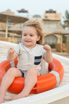 First vacation with child tips and advice. boy little kid sit on lifebuoy. toddler enjoy vacation at beach. take care about safety while travel with child. top activities for toddler at beach.