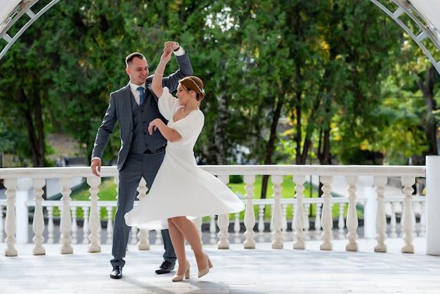 素晴らしい光と雰囲気のあるオープンエアのレストランでの新婚夫婦の最初の結婚式のダンス