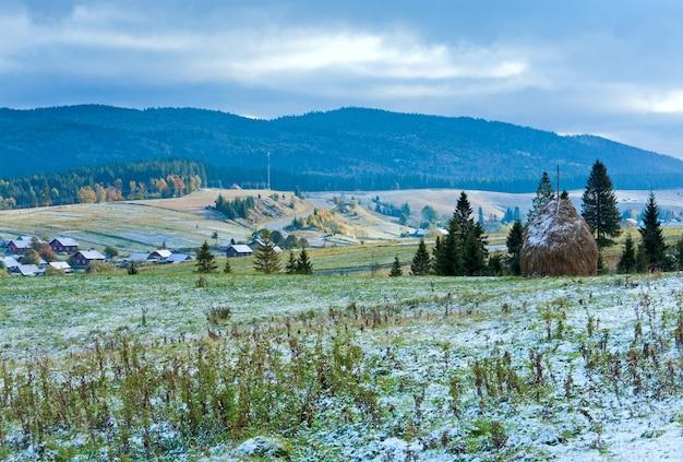 Первый зимний снег на октябрьском карпатском плато с горной деревней и шоссе вдалеке