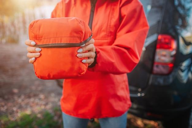 Изображение оранжевого мешка помощи firt молодое владение омана обеими руками. она стоит в палатке. модель носит оранжевую куртку.