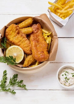Рыба и жареный картофель в миске с лимоном