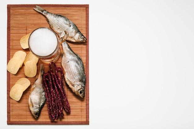 Рыба с жареным картофелем на коричневой ткани вид сверху