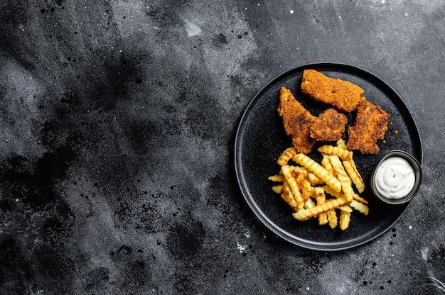 フィッシュアンドチップス、伝統的な英国料理。黒の背景
