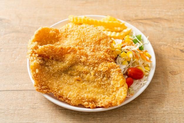 Рыба с жареным картофелем с мини-салатом на белой тарелке