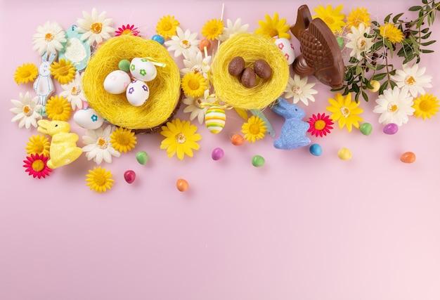 書くスペースのある上面図から見たピンクの背景にイースターの装飾が施された魚とミルクチョコレートの卵