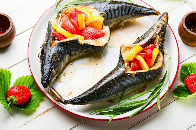 Fish baked with berries and lemon in the plate.summer fish dish,baked mackerel.