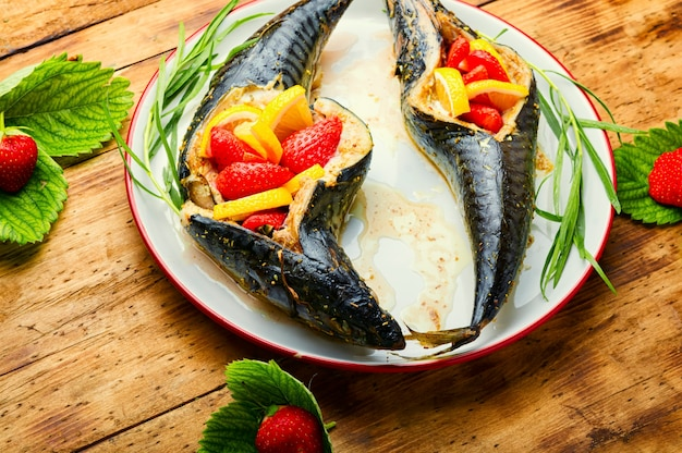 Fish baked with strawberry and lemon in the plate.summer fish dish,baked mackerel.