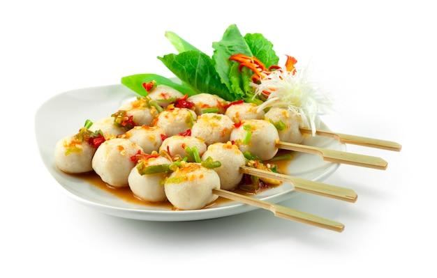 串焼きにスパイシーソースをかけたフィッシュボールが野菜のサイドビューを飾る