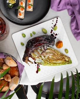 Шашлык из рыбы с зеленым соусом в белой тарелке.