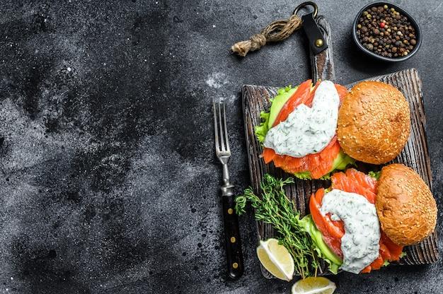 Рыбный бургер с малосольным лососем, авокадо, горчичным соусом, огурцом и салатом айсберг. черный фон. вид сверху. скопируйте пространство.