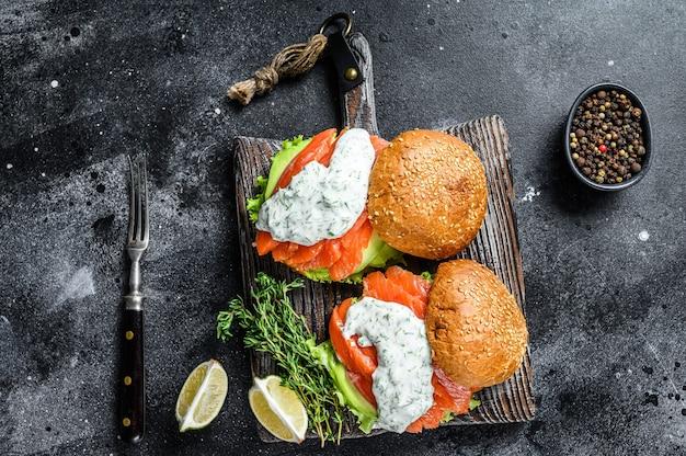 Рыбный бургер с малосольным лососем, авокадо, горчичным соусом, огурцом и салатом айсберг