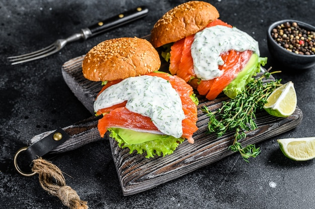 Fish burger with salted salmon, avocado, mustard sauce, cucumber and iceberg salad. black background. top view.