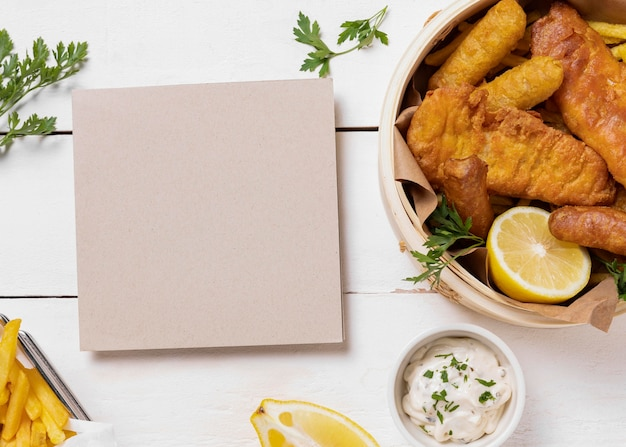 Fish and chips in bowl with lemon and card