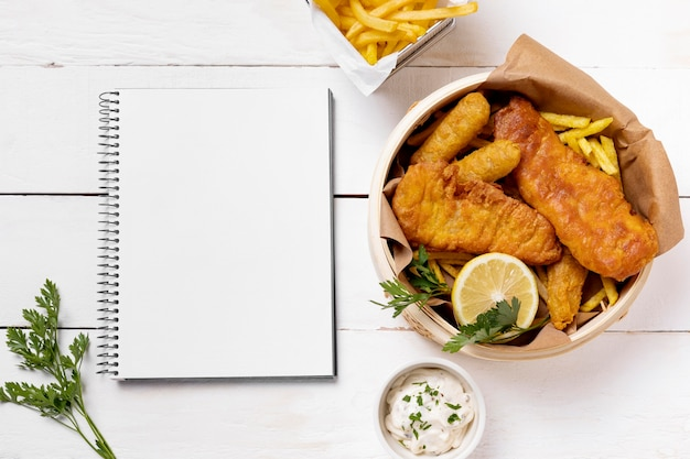 Fish and chips in bowl with lemon and notebook