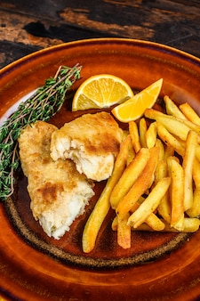 Fish and chips british fast food with french fries and tartar sauce on a rustic plate