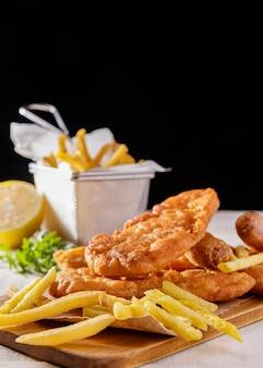 Pesce e patatine fritte sul tagliere con limone e copia spazio