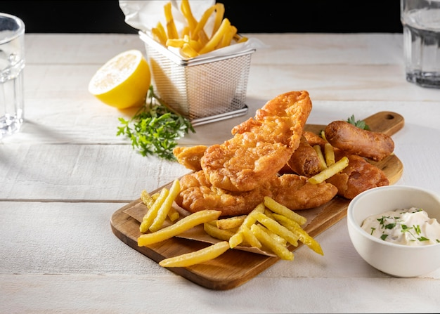 Fish and chips on chopping board with lemon and sauce