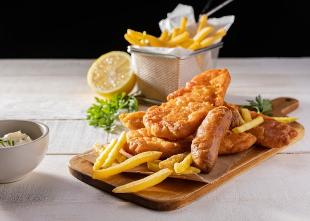 Fish and chips on chopping board with lemon