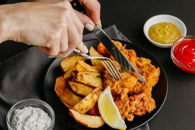 Pesce e patatine fritte sulla piastra con fetta di limone e donna con posate