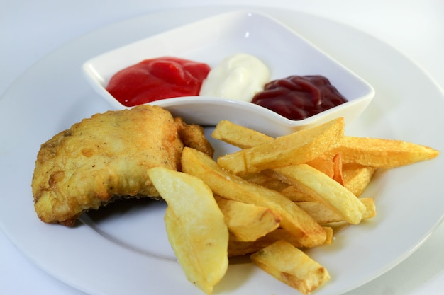 Fish  chips with chili sauce and mayonnaise on white background