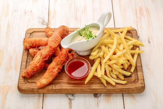 Fish and chips with different sauces on a wooden board