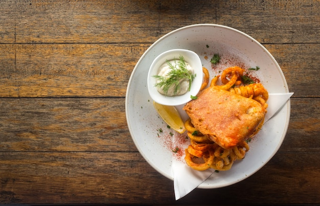 Fish and chips with tartar sauce in a plate on a wooden table.