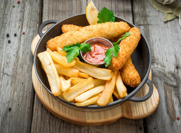 Fish and chips on wooden table, tasty food.