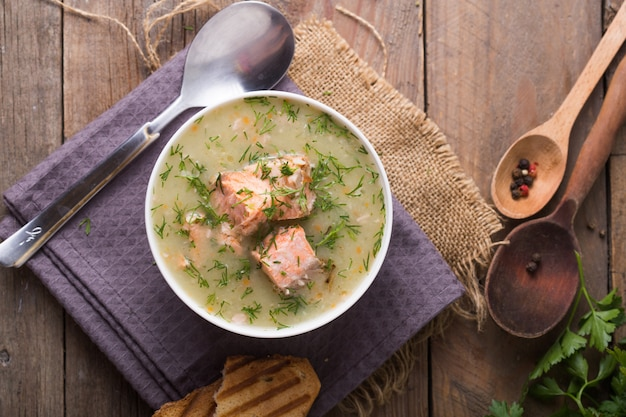 Fish cream soup with salmon, cheese, potatoes and herbs in white soup bowls