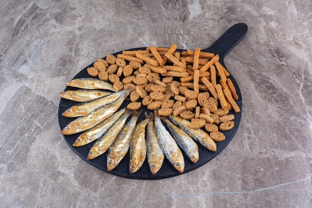 Fish and crunchy crackers on dark board. high quality photo