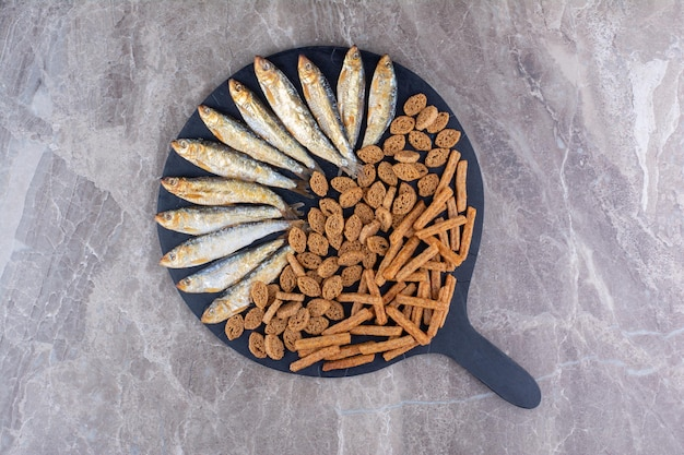 Fish and crunchy crackers on dark board