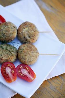 Рыбные котлеты на палочках с помидором
