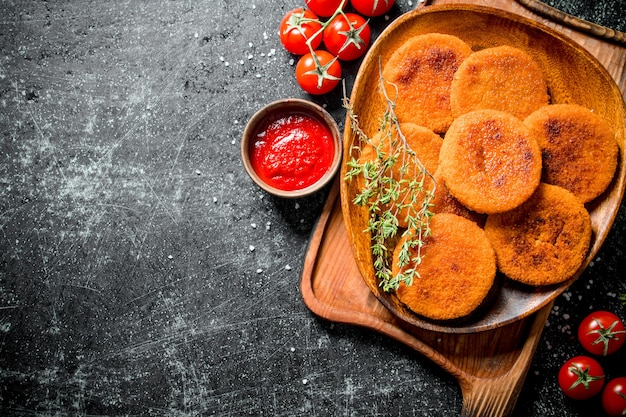 Fish cutlets on a plate with thyme,tomatoes and sauce. on black rustic