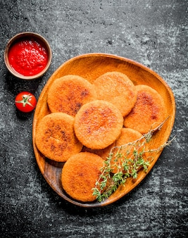 Fish cutlets with thyme and tomato sauce. on black rustic